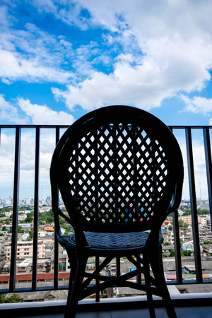 The silhouette of chair at balcony with blue sky in background Stockfoto