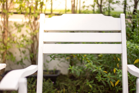 Close up white chair in the garden with sunlight