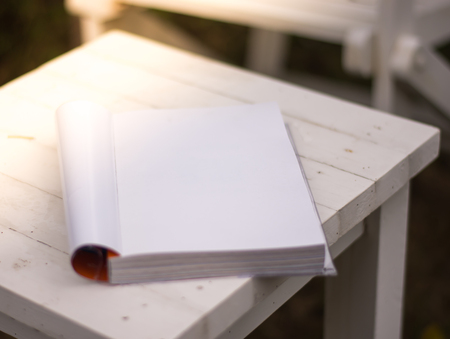 Close up the white book on the table in garden with sun light 版權商用圖片