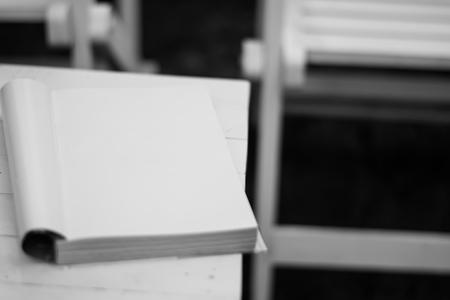 Black and white of book on the table in garden with sun light