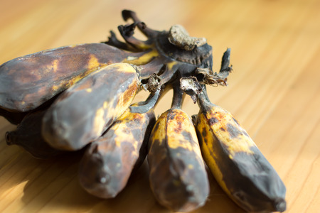The banana rot on the wooden table with sunlight 版權商用圖片