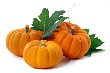 pumpkins: Three pumpkins and leaves, isolated.