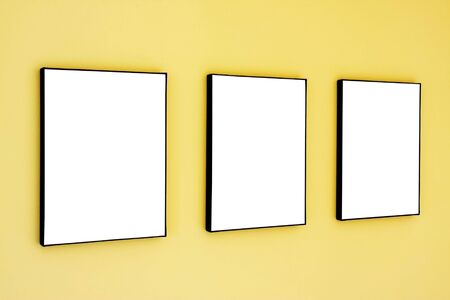 Three blank frames on a yellow wall. Фото со стока