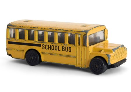 Close-up of an old and battered diecast toy school bus. photo