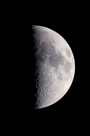 First quarter moon, photographed at the prime focus of a C5 telescope, with craters and surface details visible.