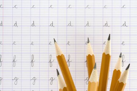 School : Pencils in front of an alphabet exercise book.