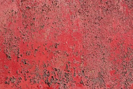 Peeling red paint on a rusted metal surface.