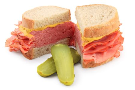 Macro of a smoked meat sandwich, cut in half, with pickles, isolated on white background.