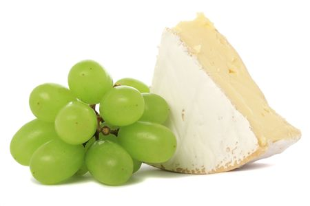 A wedge of camembert cheese with green grapes, isolated on white background.