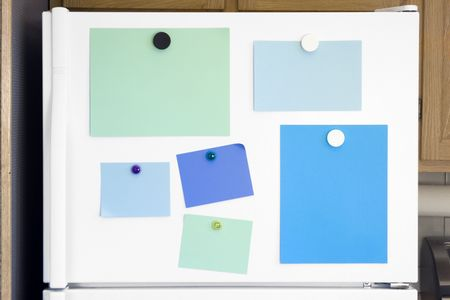 calamita: Frigorifero bianco porta con note colorate per gli elenchi e i messaggi, inviati con magneti. Archivio Fotografico