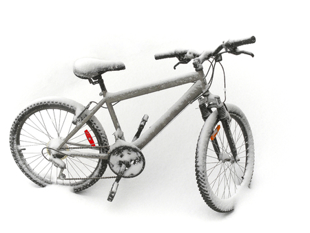 Snow covered bicycle Фото со стока
