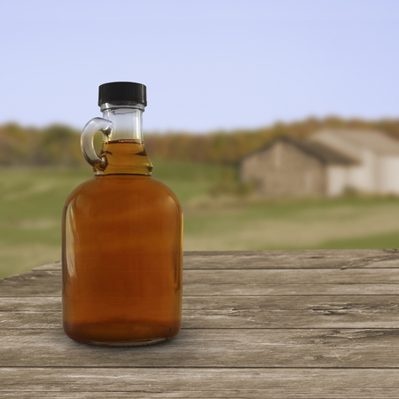 Jug of maple syrup outside on a table Фото со стока