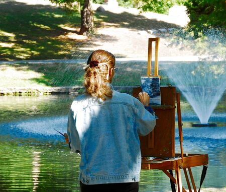 woman artist painting in sunny cemetery Stock Photo