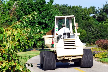 loader: maintenance man driving front loader in cemetery