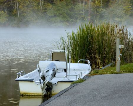 boat tied to the shore on misty morning lake Banco de Imagens