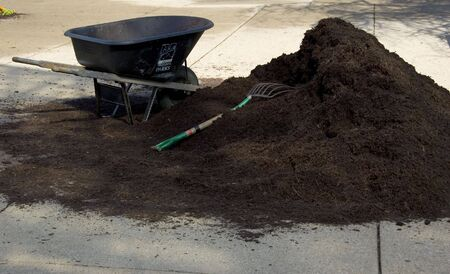 large mulch pile with pitchfork and wheelbarrow