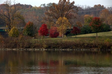 bright autumn colors reflect in park lake
