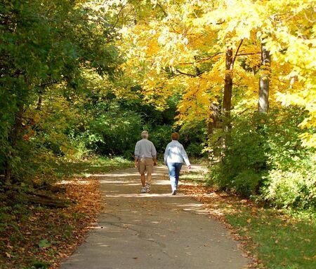 couple hiking: senior couple walking among  golden autumn trees  Stock Photo