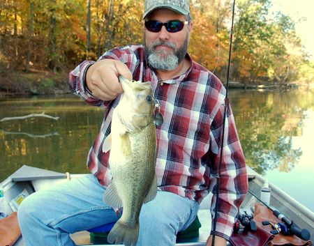 fisherman holding a large mouth bass closeup Imagens