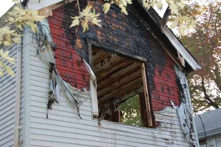 fire damage: fire damaged home with melted siding and broken glass Stock Photo