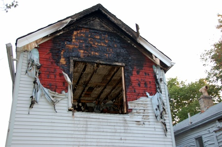 fire damaged home with melted siding and broken glass Stock Photo