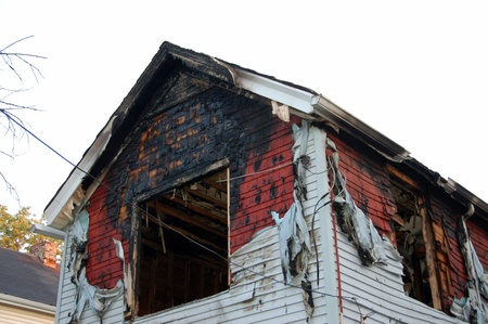 fire damaged home with melted siding and broken glass Imagens