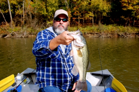 bearded fisherman holding large mouth bass closeup