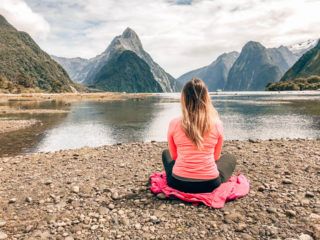 Woman wearing pink sweatshirt and black pants sitting on pink jacket laid on ground beside lake with mountains
