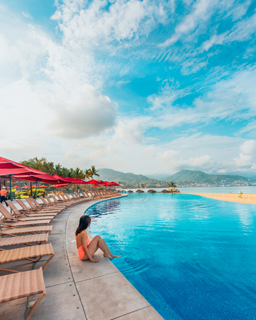 Woman sitting at swimming pool area LANG_EVOIMAGES