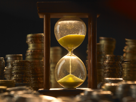 hourglass by coin stacks