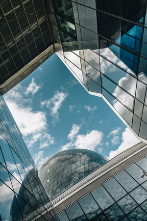 low-angle photography of grey building under blue and white sky