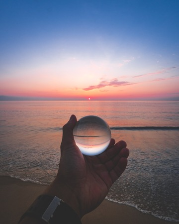 person holding clear glass ball near seashore
