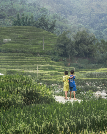 two children walking on pathway to rice terraces Stock Photo