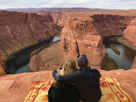man and woman sitting on carpet in front of Horseshoe Bend