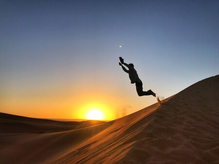 man jumping on sand