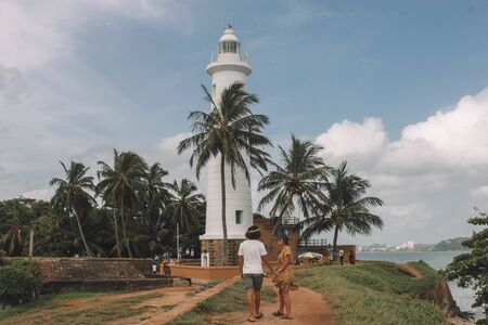 man and woman walking towards white lighthouse near body of water during daytime