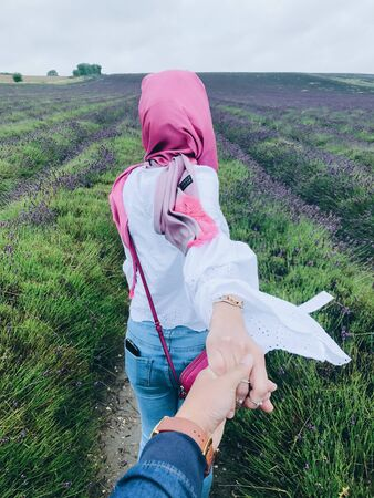 man holding woman hand surrounded by lavender flowers under cloudy sky during daytime