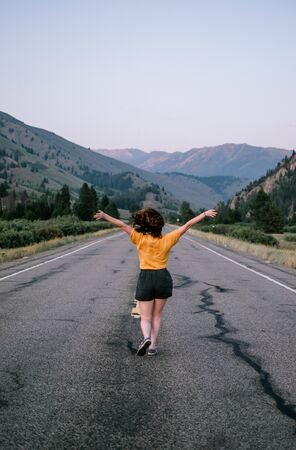 girl standing at the middle of the road while her both hands raising above Stock fotó