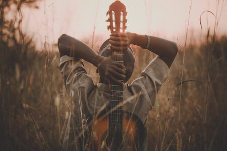 man holding classical guitar while sitting on grass field Stock fotó