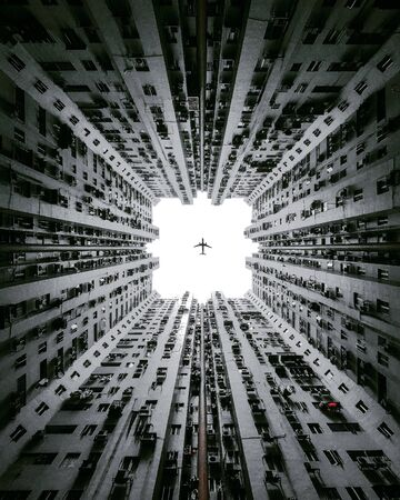 low angle photography of airliner passing through buildings