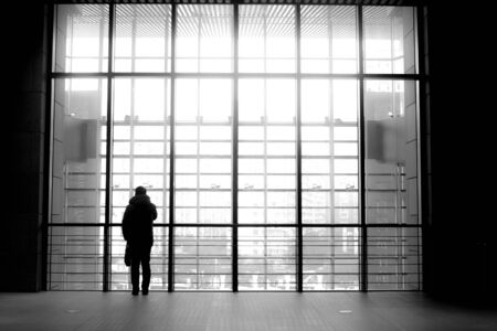 person standing against glass wall