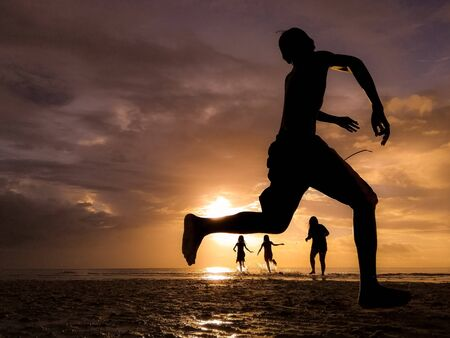 silhouette of kids playing on shore