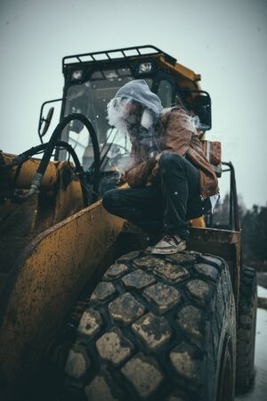 person wearing hoodie covered with smoke squatting on heavy equipment tire