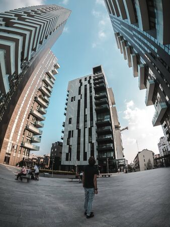 person standing between concrete buildings