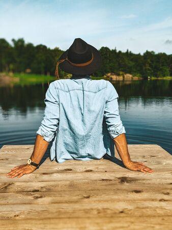 person sitting on beige sea dock facing body of water Stok Fotoğraf