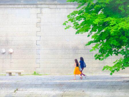 Two ladies walk on road