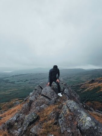 standing man on rocky cliff across plains Stock Photo