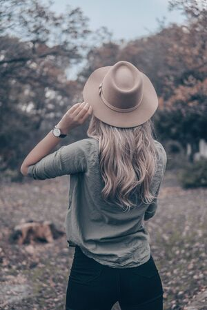 woman in brown hat near trees