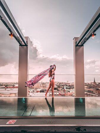 woman in monokini standing near clear glass fence