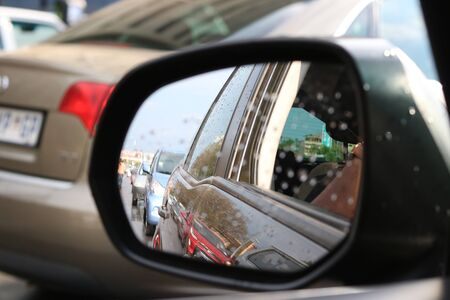A close up of a cars rear view mirror with rain spots on it. Фото со стока